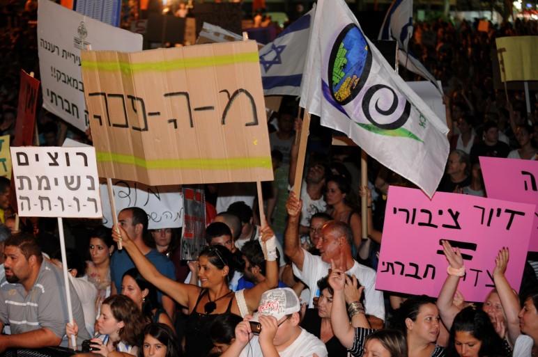 """מפגיניםות במחאה החברתית 2012 עם שלט """"מ-ה-פכה"""""""